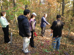 森の中に落葉で堆肥場を作るねらいを説明する山本貴紀さん。