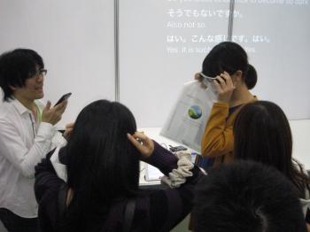 スマートフォンを使った音声認識アプリでノートテイクを実現するシステムを体験している学生たち
