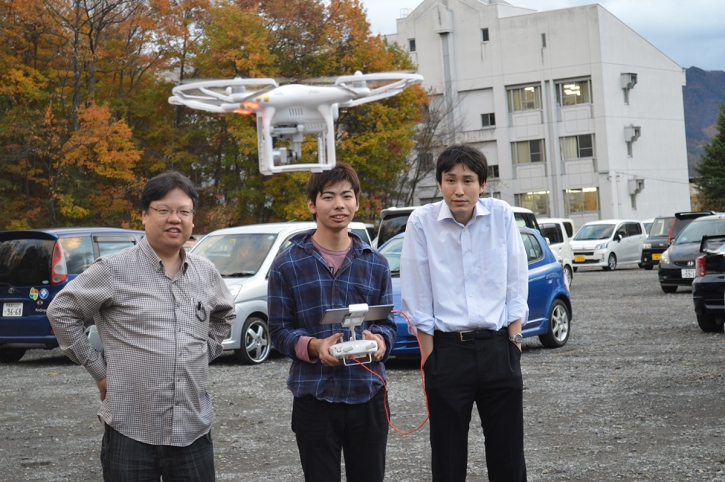 ドローンの試運転を行っている本学学生、田中教授、望月助教の3名