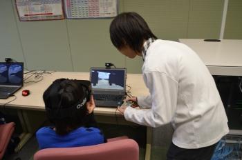3D眼鏡を用いた没入空間システムの操作方法を指導している本学学生