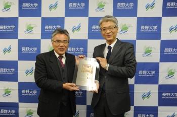 記念の楯を受け取る田口事務局長(左)