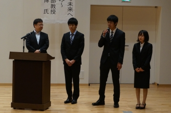 取組について説明する田中教授と代表の企業情報学部の学生