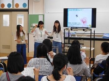 指文字を教える学生たち