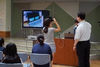 本学の学生が開発したシステムで没入空間を体験する小学生(体験授業にて)
