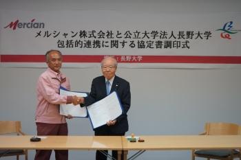 協定締結後に握手を交わす松尾ゼネラル・マネージャーと白井理事長